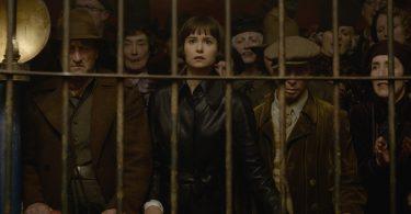 Tina e uma plateia olha para o que está dentro de uma jaula.