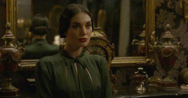 Vinda Rosier, muito bem arrumada, numa casa bem decorada, com um espelho grande e dourado, relógio e outras antiguidades.