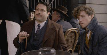 Newt e Jacob sentados no café Arbinger, um café trouxa em Paris. Jacob se apoia em um guarda-chuva.