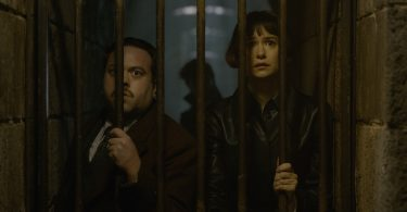 Tina e Jacob por trás de grades de um corredor subterrâneo. Newt está atrás deles.