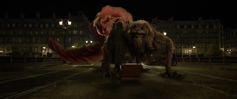 Newt agita algo para o zouwu no meio da rua, possivelmente para atraí-lo para dentro de sua melta.
