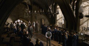 Dumbledore é visitado por oficiais do Ministério no meio de sua aula. Há várias crianças dos dois lados da sala, ele está ao meio, e acabaram de chegar pessoas do Ministério pela porta.