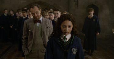 Jovem Leta é incentivada por Dumbledore a enfrentar o bicho-papão. Jovem Newt estão afastado, do lado, e uma grande turma está atrás da garota.