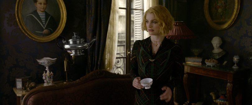 Queenie segura uma xícara numa casa bem decorada, há quadros variados, estátuas, várias antiguidades. Um bule está levitando.