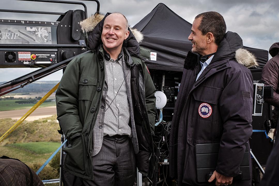 Foto de Yates e Heyman ao lado de vários equipamentos de filmagens numa locação a céu aberto. Os dois riem.
