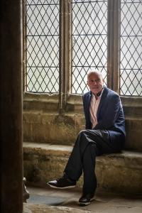 Foto de David Yates sentado em um banco de pedra no cenário de Hogwarts.