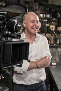 Foto de David Yates atrás de uma câmera no cenário da casa do Nicolau Flamel. Ele sorri e tem os braços cruzados.