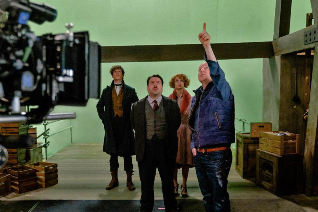 Foto de David Yates apontando para o alto, pra onde os atores Dan Fogler, Eddie Redmayne e Alison Sudol olham. Eles estão em frente a uma parede verde.
