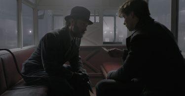Dumbledore conversa com Newt em um ônibus.
