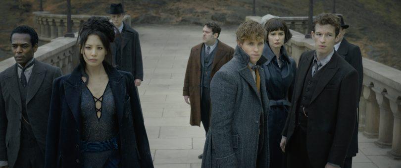 Yusuf Kama, Nagini, Jacob, Newt, Tina, Teseu e dois outros bruxos estão no começo da ponte que se contecta a Hogwarts.
