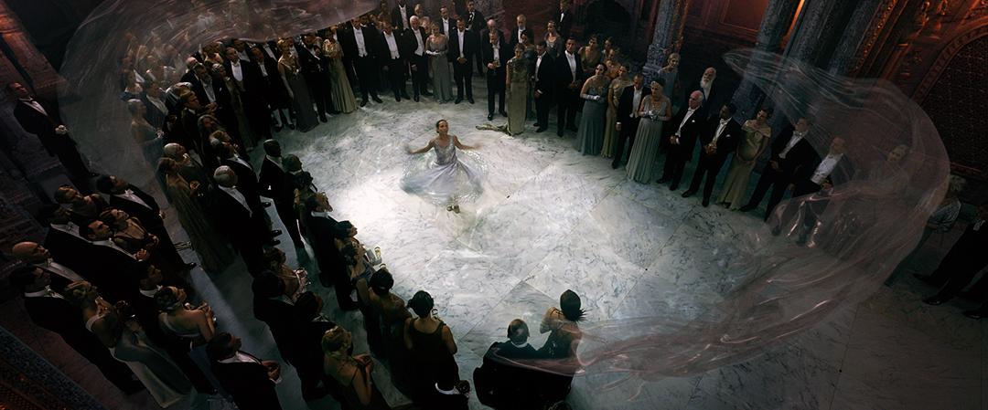Frame da cena. O salão é visto de cima. No centro, a dançarina, e em volta, os convidados.