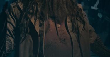Hagrid com seus óculos de proteção de motoqueiro em sua testa, segurando um guarda-chuva.