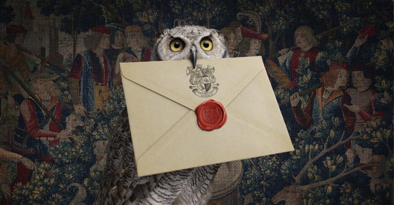 """Fundo escuro com tapeçaria em tons predominantemente azuis retratando cena medieval. Superfície de madeira antiga com poleiro de cobre e madeira em que uma coruja está pousada. A ave segura um envelope amarelado no bico, no qual há um selo de cera vermelha e o brasão do """"Instituto Mágico de Podcasts Estação 9¾""""."""