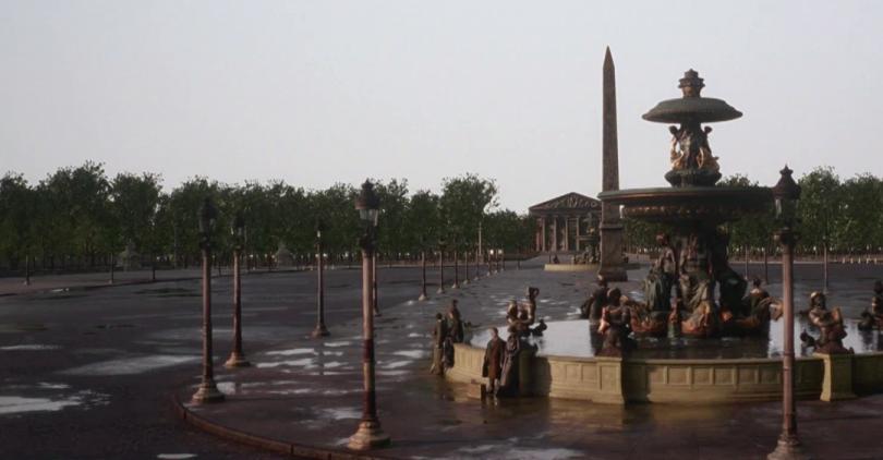 Plano geral da cena mostra a praça e, ao fundo, árvores.