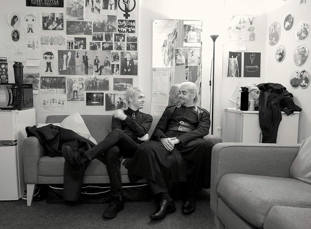 Foto de bastidores dos atores intérpretes de Escórpio e Draco sentados num sofá e conversando amistosamente. Na parede atrás do sofá há diversos rascunhos, desenhos e fotos relacionados à peça.