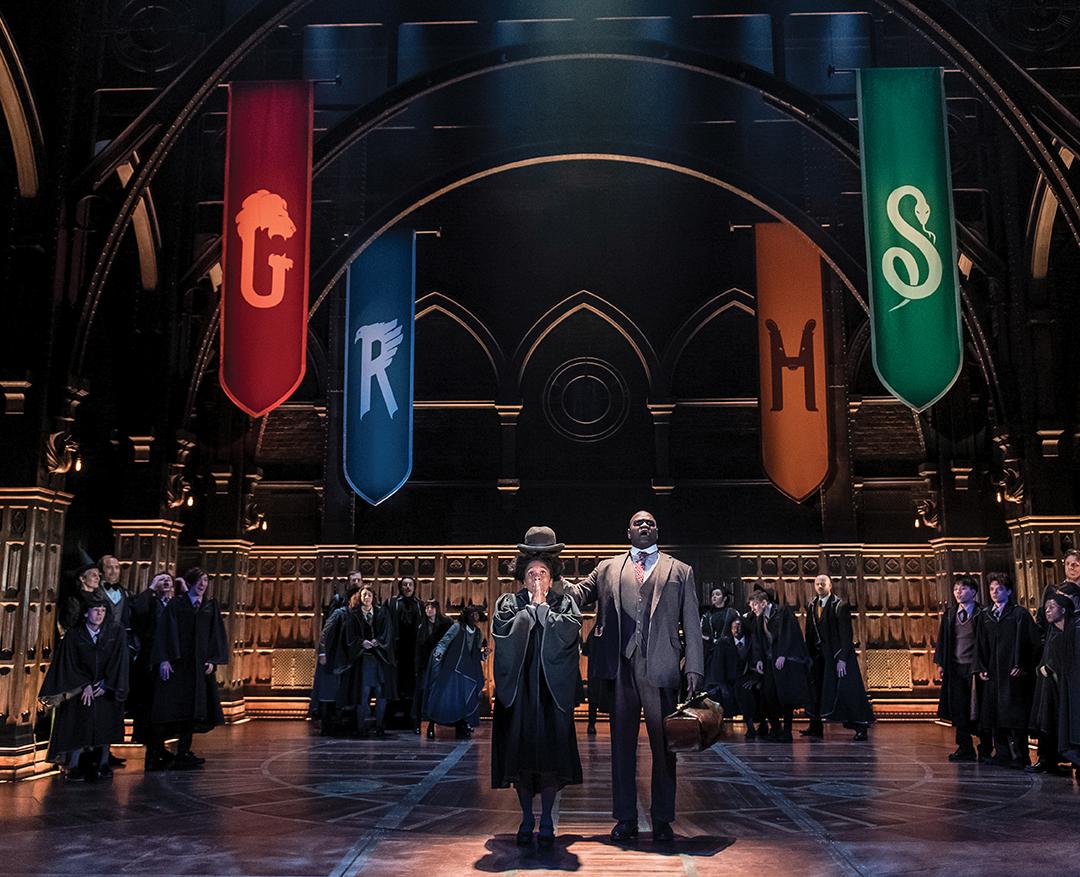 Foto da cena da seleção de Rose Granger-Weasley. Ela está no centro do palco e o ator do chapéu seletor coloca um chapéu coco em sua cabeça. Ao redor, outros alunos observam, e em cima, há quatro bandeiras, cada uma de uma casa de Hogwarts.
