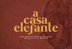 """O logotipo do podcast """"A Casa Elefante"""" aparece em amarelo sobre um fundo vermelho e com a ilustração de um elefante. Embaixo do logo, o texto """"Uma releitura, capítulo a capítulo, da obra de J.K. Rowling.""""."""