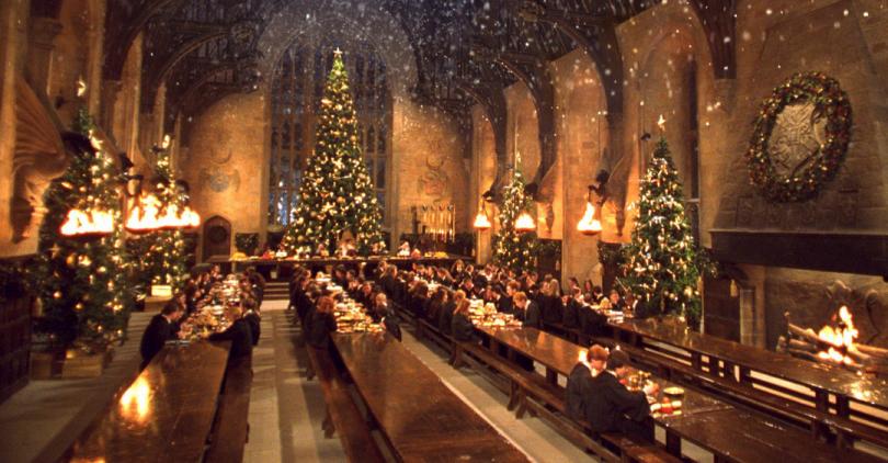 O Salão Principal de Hogwarts no Natal, com uma árvore de Natal no fundo e alguns alunos sentados nas mesas de suas Casas.