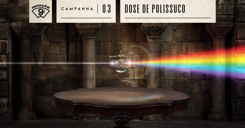 """Fundo escuro com parede e arcos de pedras. À frente, mesa oval de madeira com detalhes entalhados. Flutuando sobre ela, há uma maçã de cristal. Pelo lado esquerdo, o objeto recebe um pequeno fio de luz branco que, pelo lado contrário, se expande num grande flash de luzes com as cores do arco-íris. Na parte superior, temos o logo do podcast """"Estação 9 ¾"""", e os dizeres """"Campanha 03 - Dose de Polissuco""""."""