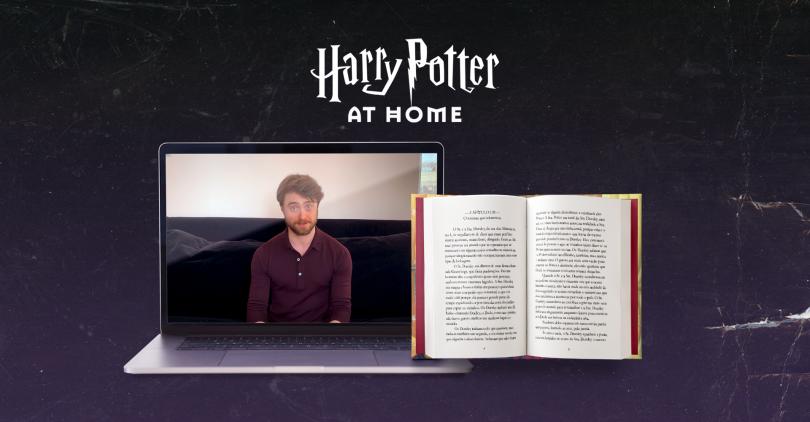 Foto de um computador reproduzindo o vídeo com Daniel Radcliffe, e do lado dele o livro Harry Potter e a Pedra Filosofal aberto no primeiro capítulo.