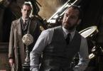 Na foto, vemos Dumbledore (Jude Law) e uma pessoa desconhecida ao fundo. Alvo Dumbledore usa um paletó sem terno: colete e calça cinzas, camisa cinza claro ou azul claro, gravata preta. Ele está encostado, com as mãos no bolso da calça, em uma mesa, que contém um objeto de formato arredondado, cheio de buracos, de cor de osso. Ao lado da mesa, vemos alguns livros empilhados. Por trás do homem desconhecido, um instrumento dourado com o que parece ser uma lente de aumento em uma das pontas. O homem desconhecido está vestido de sobretudo texturizado e marrom e segura algo em uma de suas mãos. Os dois olham para o mesmo interlocutor.