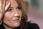 Foto em close de Rowling no início da fama, com a mão segurando a cabeça e um sorriso tímido.
