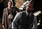 """Imagem promocional de """"Os Crimes de Grindelwald"""": Dumbledore (Jude Law) se apoia numa mesa da sala de Defesa Contra as artes das trevas. Ele usa um terno sem paletó. Ao fundo, uma pessoa do ministério da magia"""