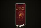 Foto de um celular com fones de ouvido embaixo. Na tela aparece a capa de Harry Potter e a Pedra Filosofal.