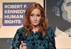 J.K. Rowling falando em um palanque de um prêmio. Ela usa um vestido verde e tem o cabelo ruivo.