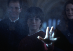 Imagem do filme Harry Potter e a Pedra Filosofal. Reflexo de Harry olhando no espelho de Ojesed. Ele vê seus pais e está erguendo os braços para tocá-los, mas apenas toca o vidro. Seus pais sorriem ao fundo.