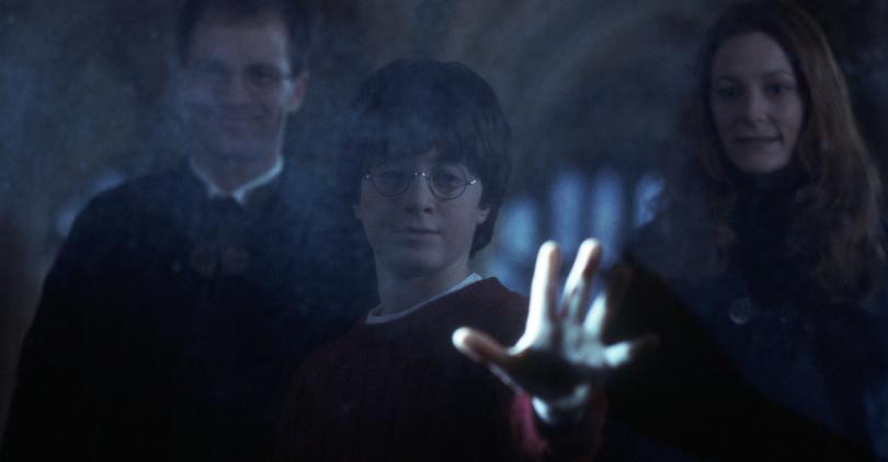 Imagem do filme Harry Potter e a Pedra Filosofal. Reflexo de Harry olhando no espelho de Ojesed. Ele vê seus pais e está erguendo os braços para tocá-los, mas apenas toca o vidro. Seus pais sorriem ao fundo.